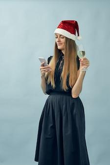 Dziewczyna z lampką szampana i czapką świętego mikołaja