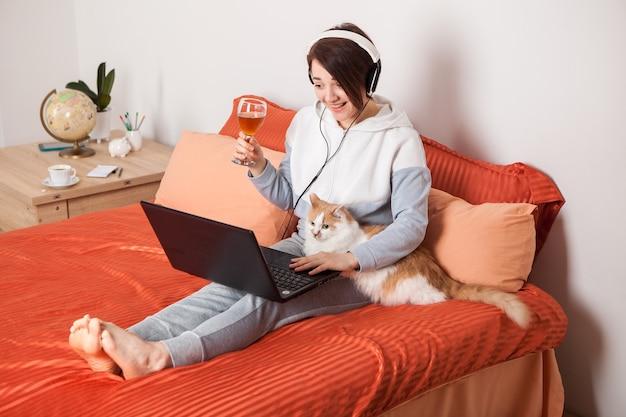 Dziewczyna z lampką wina komunikuje się online z przyjaciółmi i rodziną.