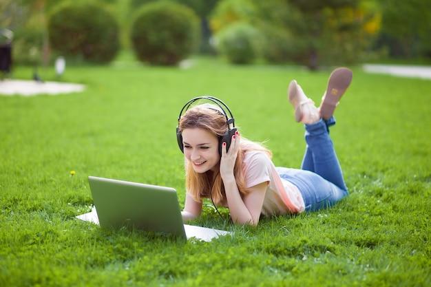 Dziewczyna z laptopa w słuchawkach leżąc na trawie