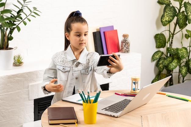 Dziewczyna z laptopem i smartfonem przy selfie lub po rozmowie wideo w domu