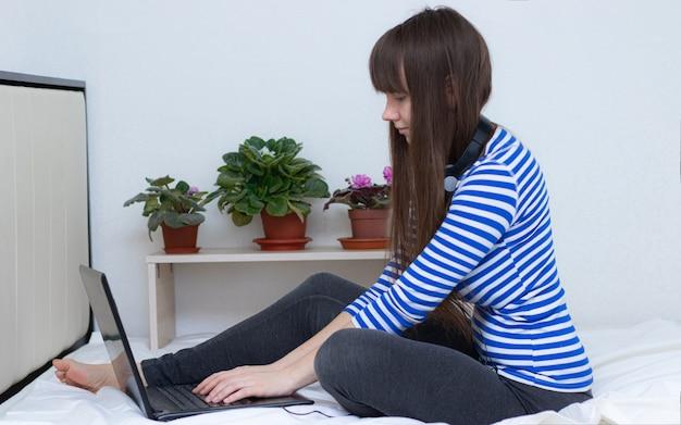 Dziewczyna z laptopem na łóżku. praca zdalna . zdrowie i bezpieczeństwo . dziewczyna i praca zdalna. koronawirus.