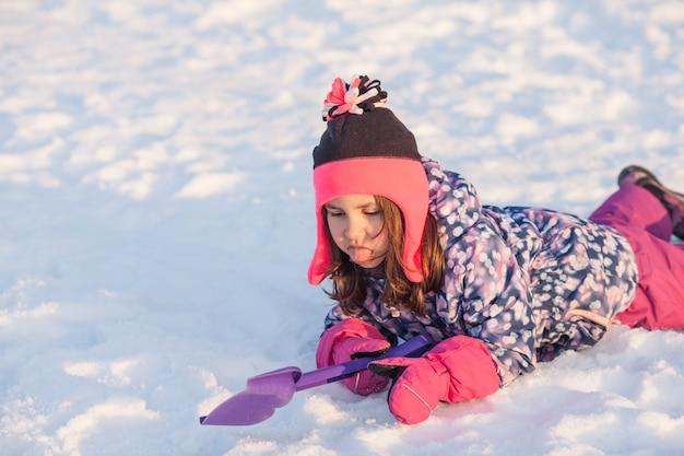 Dziewczyna z łopatą leżała na śniegu