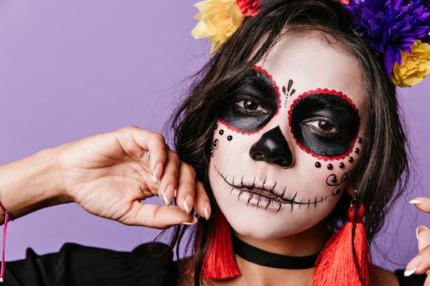 Dziewczyna z magicznym wyglądem stawia na fioletowej ścianie. kobieta z kwiatami we włosach wystrojona na halloween.