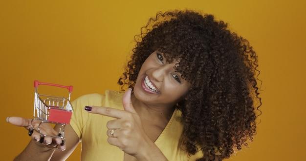 Dziewczyna z małą kartą na zakupy. uśmiechnięta i tańcząca kobieta kręcone włosy w koncepcji zakupy. młoda kobieta z miniaturowym wózkiem. e-commerce i biznes. samochód na zakupy. kobieta kupujący. żółte tło.