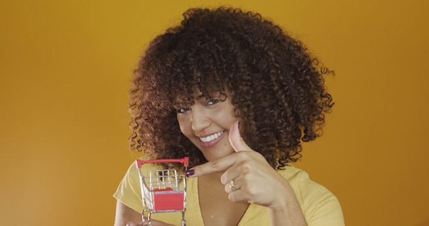 Dziewczyna z małą kartą na zakupy uśmiechnięta i tańcząca kobieta z kręconymi włosami w koncepcji zakupów