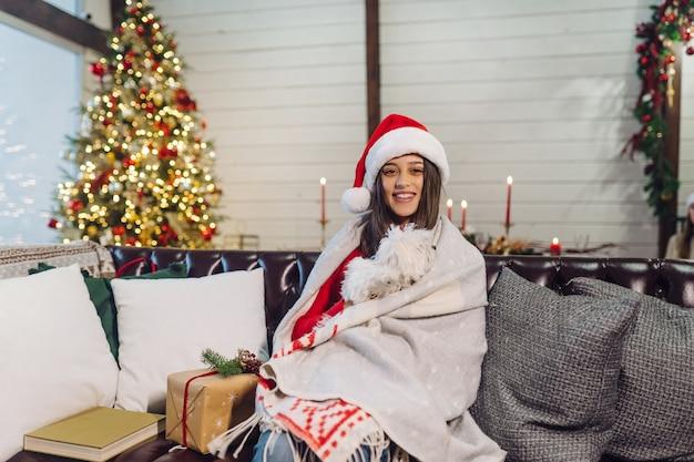 Dziewczyna z małym psem w ramionach siedzi na kanapie w sylwestra.