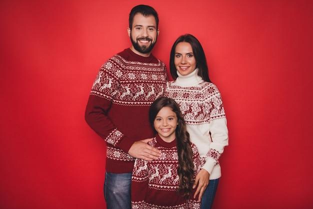 Dziewczyna z mamą i tatą w przytulających się uroczych, tradycyjnych strojach bożonarodzeniowych z dzianiny