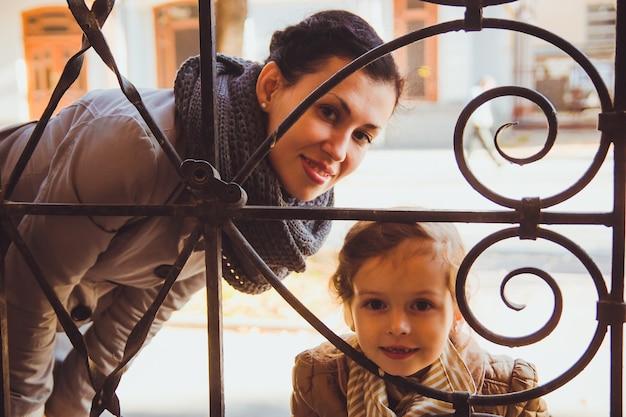 Dziewczyna z mamą wyglądającą przez okno starej kobiety patrzącej z córką przez wzór