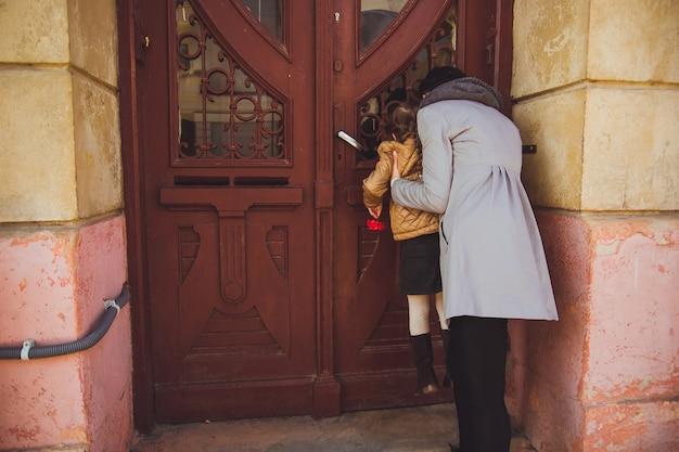 Dziewczyna z mamą wyglądającą przez okno starych drewnianych drzwi kobieta trzymająca córkę na schodach