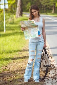 Dziewczyna z mapą i torbą w ręku, chodzenie na poboczu drogi
