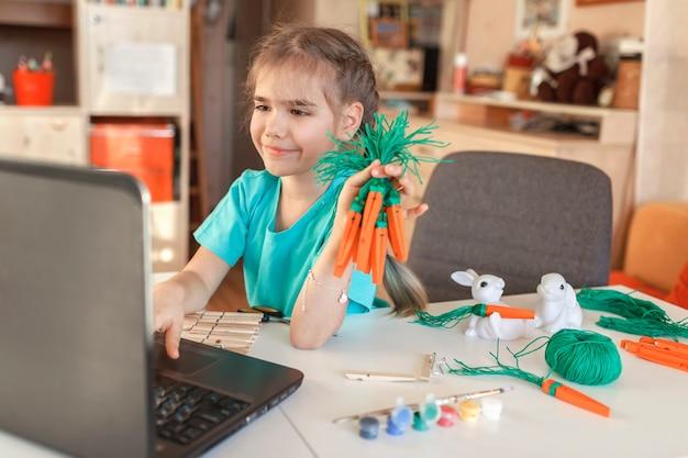 Dziewczyna z marchewką diy z drewnianymi szpilkami do ubrania wita rodzinę wielkanocą online, wakacje zero waste