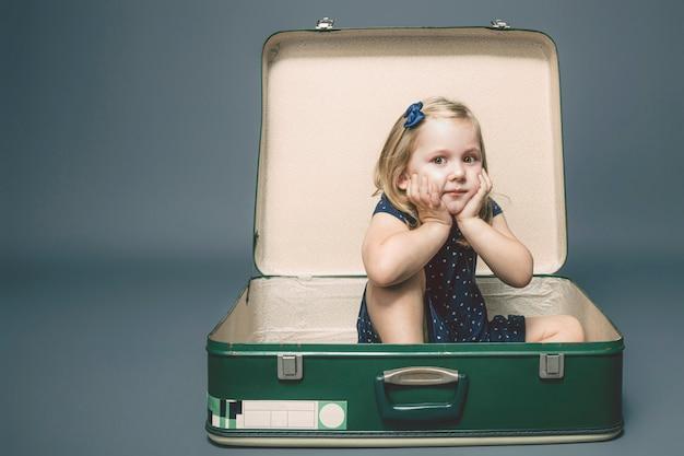 Dziewczyna z marzycielskim wyrażeniem siedzi wśrodku rocznik walizki