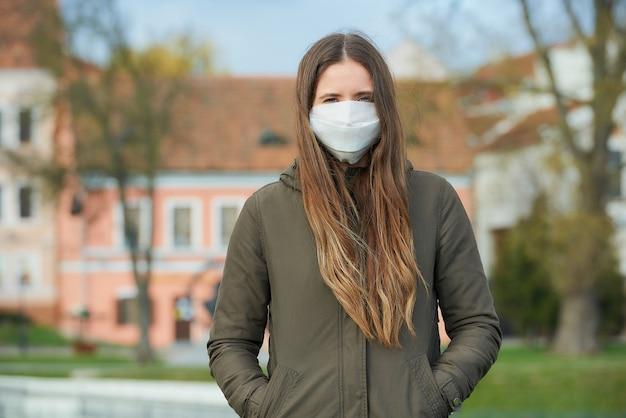 Dziewczyna z maską chirurgiczną na twarzy przeciwko covid-19 pozuje na starym mieście.