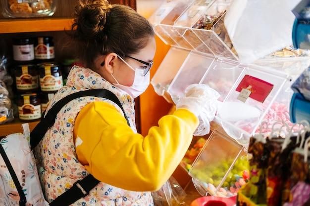 Dziewczyna z maską kupuje żelki w żółtym swetrze w sklepie
