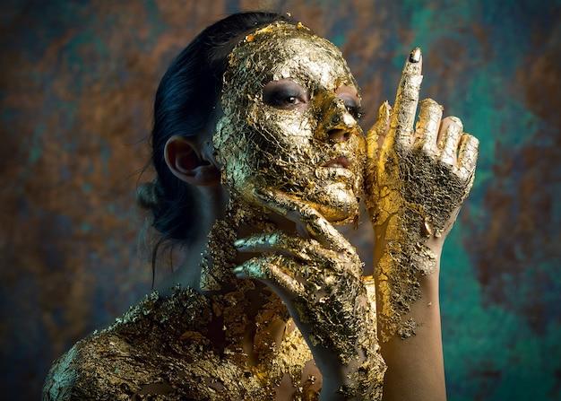 Dziewczyna z maską na twarzy wykonaną ze złotego liścia ponury portret studyjny brunetki na abstrakcie