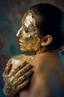 Dziewczyna z maską na twarzy wykonaną ze złotego liścia ponury portret studyjny brunetki