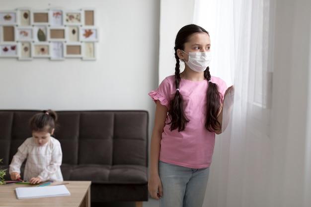 Dziewczyna z maską, patrząc przez okno