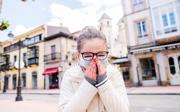 Dziewczyna z maską przykłada dłonie do twarzy w centrum miasta