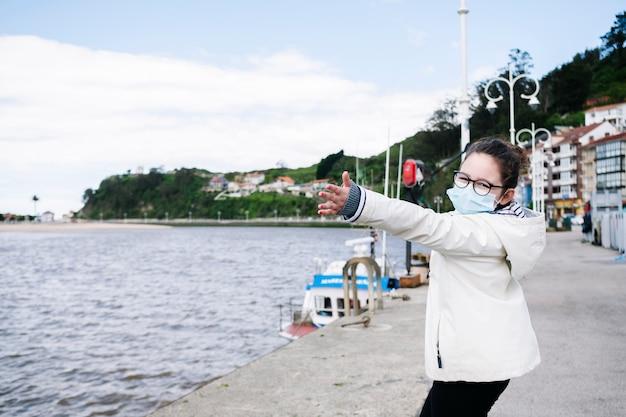 Dziewczyna z maską w porcie rybackim w mieście z otwartymi ramionami szczęścia i wolności