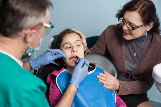 Dziewczyna z matką na pierwszej wizycie u dentysty. starszy męski dentysta robi pierwszy badaniu kontrolnemu dla pacjenta przy stomatologicznym biurem