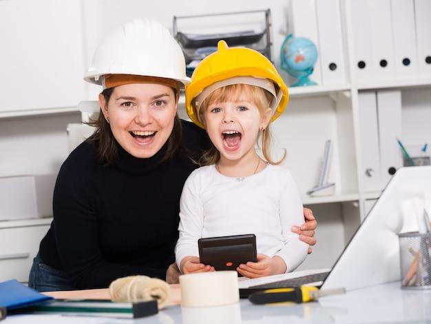 Dziewczyna z matką siedzi w pobliżu laptopa i wybierając materiały do naprawy