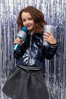 Dziewczyna z mikrofonem i szklanką napoju na imprezie