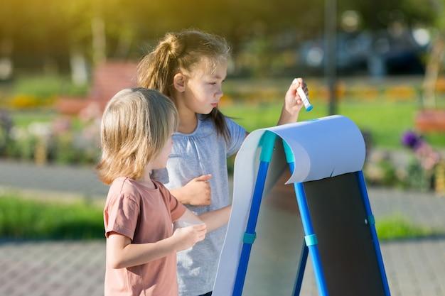 Dziewczyna z młodszym bratem rysuje farby na papierowym parku miejskim