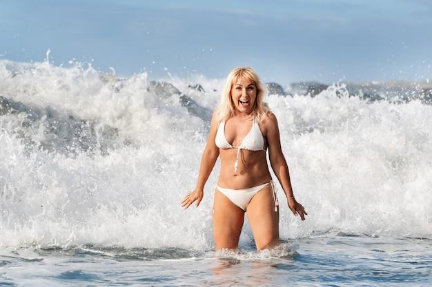 Dziewczyna z mokrymi włosami przeskakuje nad dużymi falami oceanu atlantyckiego, wokół fali z rozpryskami i kroplami wody.