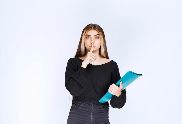 Dziewczyna z niebieską teczką prosząca o ciszę. zdjęcie wysokiej jakości
