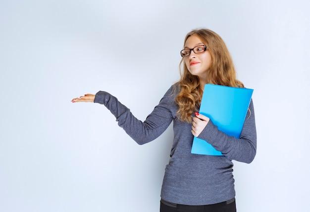 Dziewczyna z niebieską teczką, wskazując na swojego kolegę.