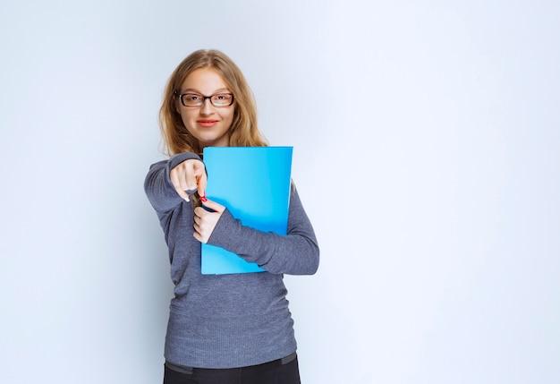 Dziewczyna z niebieską teczką wskazującą gdzieś.