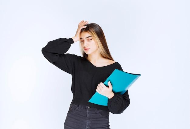 Dziewczyna z niebieskim folderem wygląda na zdezorientowaną i zamyśloną. zdjęcie wysokiej jakości