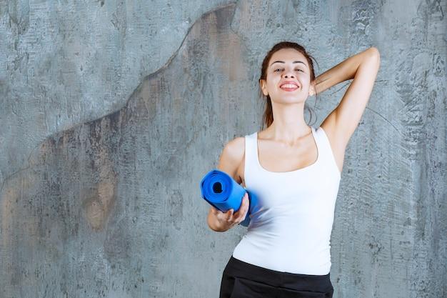 Dziewczyna z niebieskim matem do jogi czuje się szczęśliwa i pozytywna.