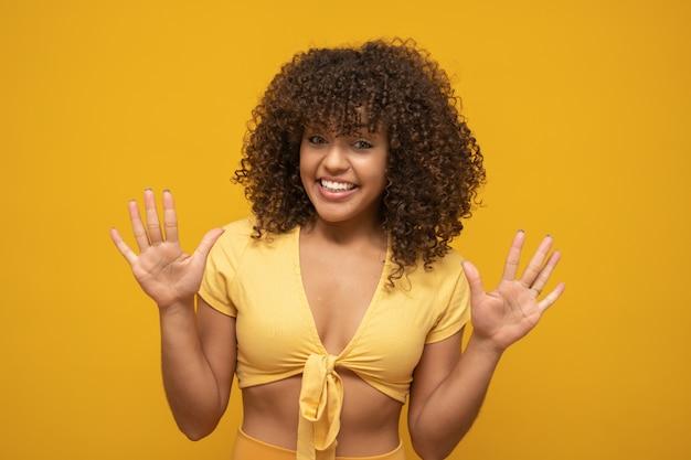 Dziewczyna z niespodzianką na twarzy z podniesionymi rękami