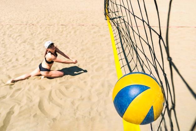 Dziewczyna z niezadowoloną miną spada na piasek wbijając piłkę do siatki. przegrana mistrzostwa w siatkówce plażowej. zawody sportowe. letnie zajęcia sportowe. upuść na piasek. siatka do siatkówki.
