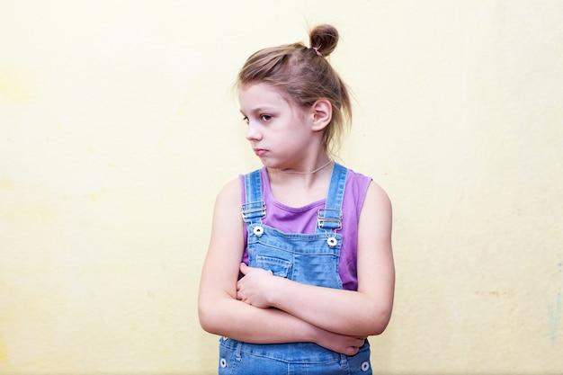 Dziewczyna z niezadowoloną twarzą, krzyżująca ramiona na piersi