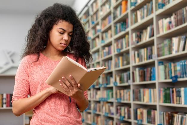 Dziewczyna z niskim kątem skoncentrowana na czytaniu