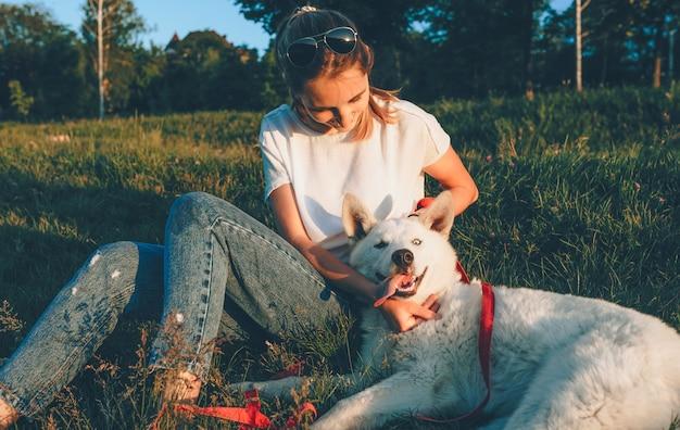 Dziewczyna z okularami przeciwsłonecznymi ma przerwę siedząc na trawie