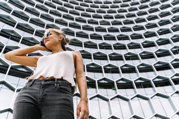 Dziewczyna z okularami przeciwsłonecznymi stoi przed nowożytnym budynkiem opowiada z wiszącą ozdobą