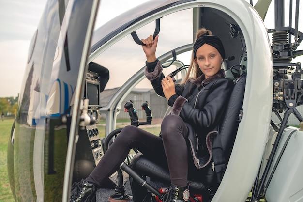 Dziewczyna z okularami przeciwsłonecznymi w ręku, siedząca na fotelu pilota w helikopterze