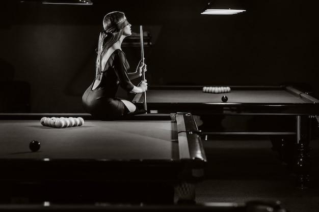 Dziewczyna z opaską na oczach i kijem w dłoniach siedzi na stole w klubie bilardowym. rosyjski bilard. czarno-białe zdjęcie.