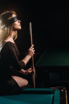 Dziewczyna z opaską na oczach i kijem w dłoniach siedzi na stole w klubie bilardowym. rosyjski bilard