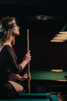 Dziewczyna z opaską na oczach i kijem w dłoniach siedzi na stole w klubie bilardowym. rosyjski bilard.
