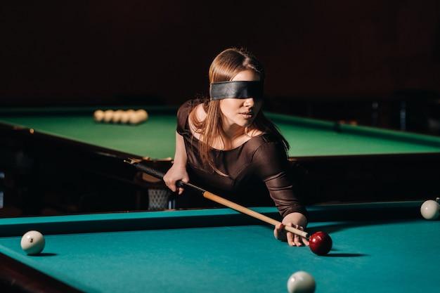 Dziewczyna z opaską na oczach i kijem w ręku w klubie bilardowym.rosyjski bilard