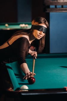 Dziewczyna z opaską na oczach i kijem w ręku w klubie bilardowym