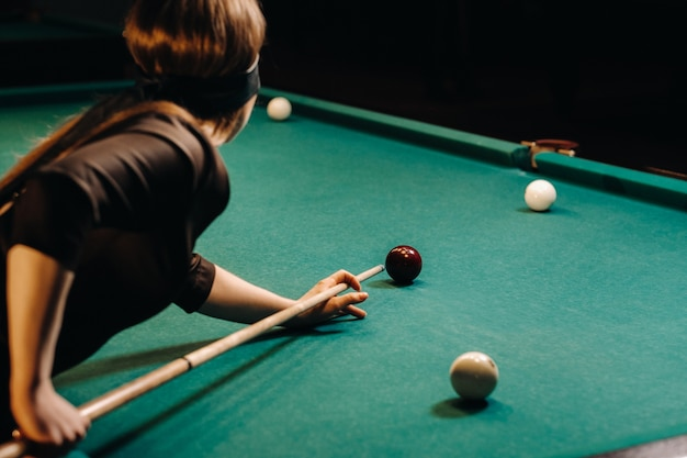 Dziewczyna z opaską na oczy i kijem w dłoniach w klubie bilardowym. rosyjski bilard.