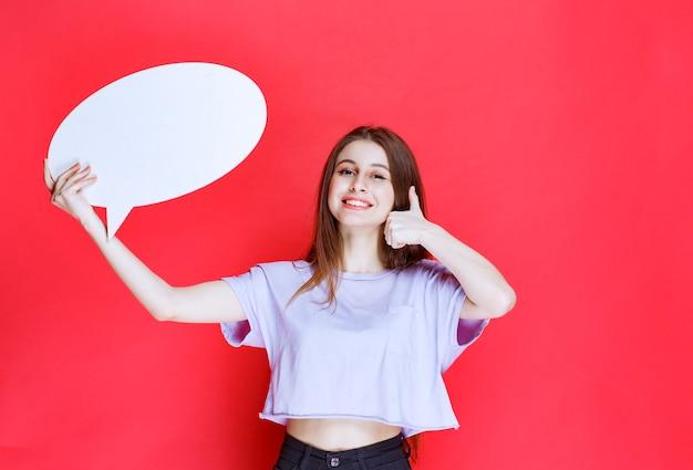 Dziewczyna z owalną tablicą infor pokazując kciuk do góry znak.