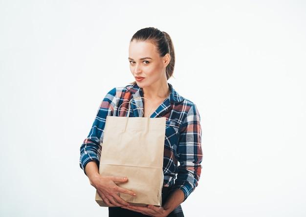 Dziewczyna z papierowymi torbami. symbol konsumpcjonizmu. zdjęcie z boku. torba papierowa w kolorze brązowym. koszula w kratkę.