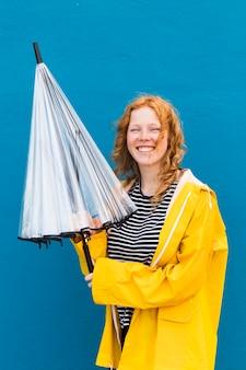 Dziewczyna z parasolem i płaszczem przeciwdeszczowym