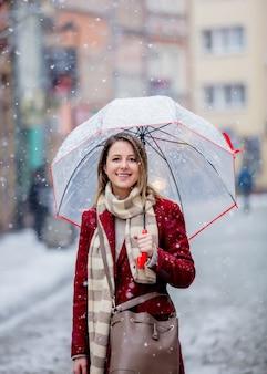 Dziewczyna z parasolowym białym śnieżnym spadaniem zostaje na miasto ulicie